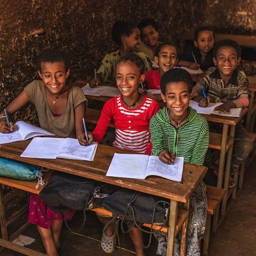 Happy Ethiopian schoolkids in their classroom